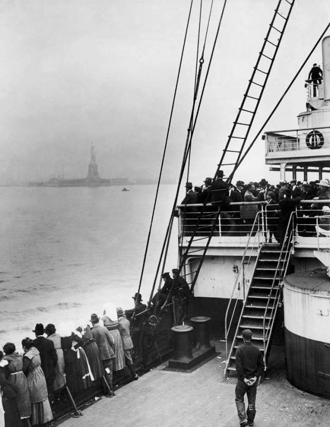Immigrants view the Statue of Liberty while entering New York harbor aboard an ocean liner en route to Ellis Island, New York City, 1910s. (Photo by Edwin Levick/Getty Images)