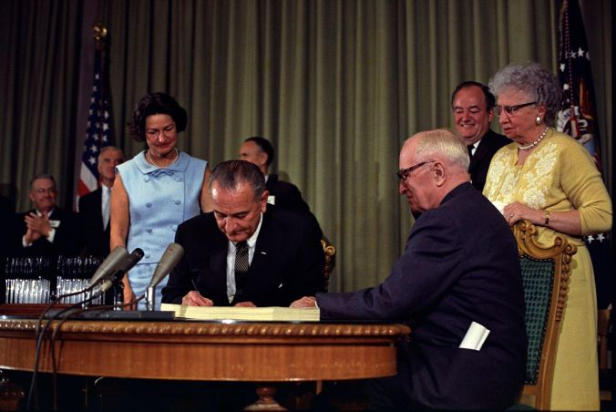 1600px-Lyndon_Johnson_signing_Medicare_bill,_with_Harry_Truman,_July_30,_1965